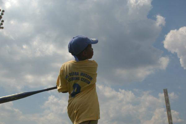 Baseball camper swinging bat