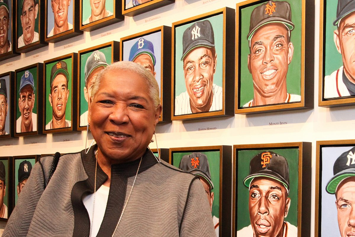 Pamela Irvin Fields with the portrait of her dad, Monte Irvin, as part of of Andy Jurinko's Golden Boys paintings