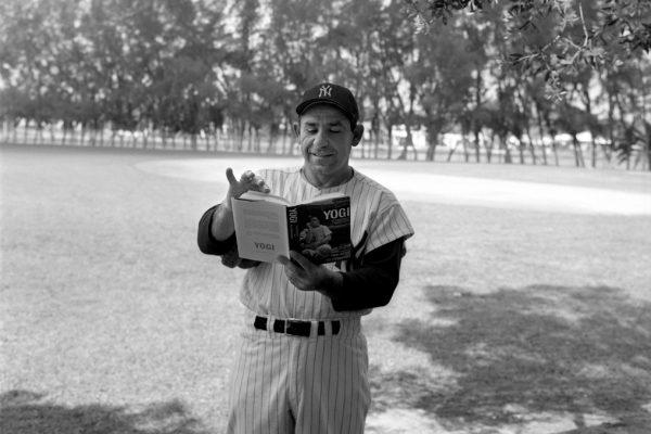 Yogi Berra in a field reading a book
