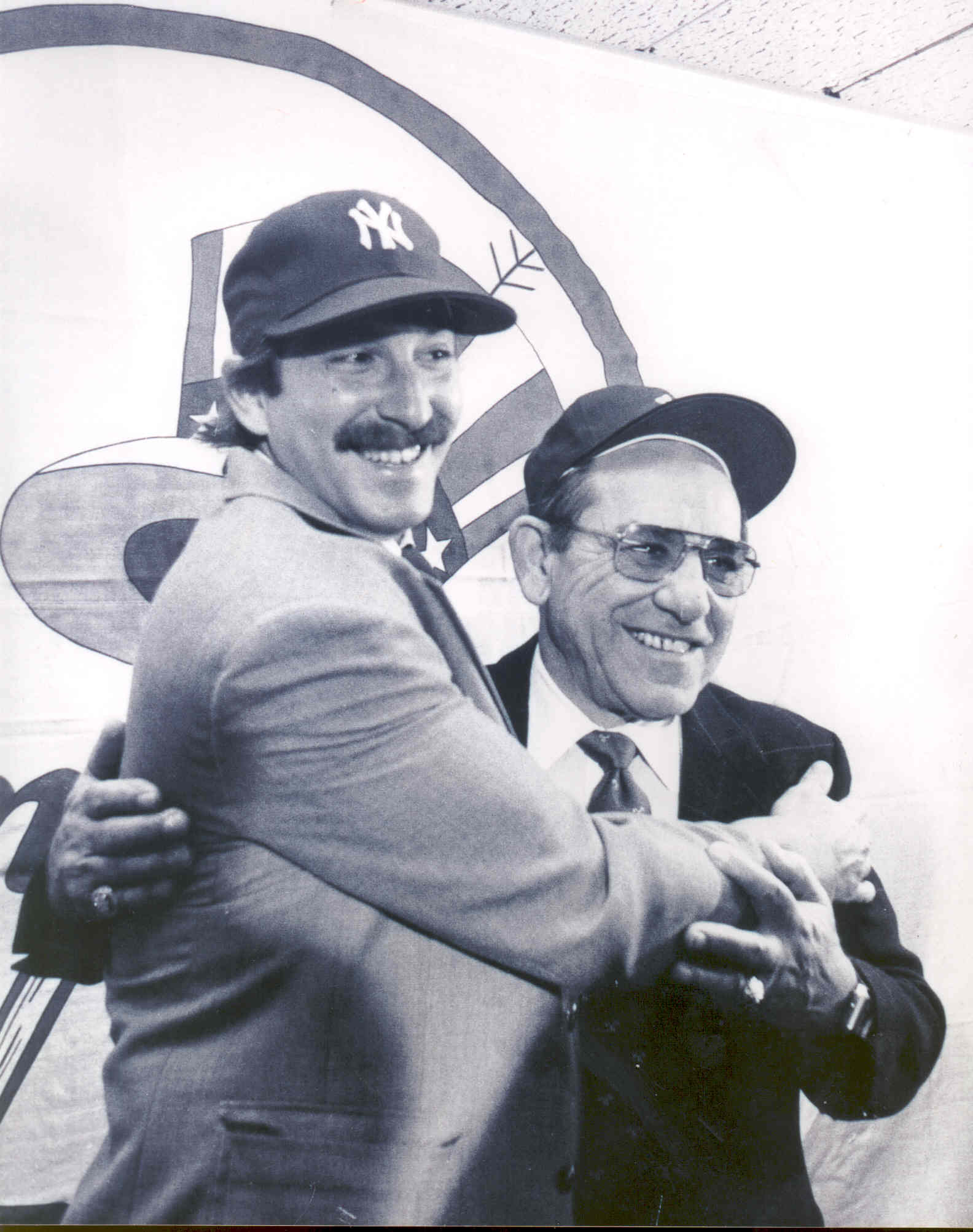 Yogi and Dale Berra hugging and posing for pictures