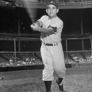 Baseball player Yogi Berra swinging bat.