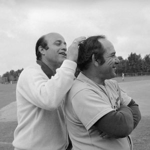 Joe Garagiola applies his expertise of hair dresser making New York Mets manager Yogi Berra in St. Petersburg, Florida, ready for a television show on March 13, 1975.   Berra will appear with Garagiola on the TV show.   Boyhood pals in St. Louis, both are at the pinnacle of careers. (AP Photo)
