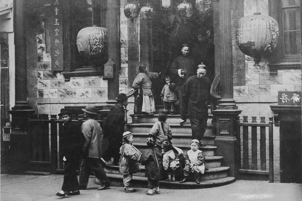 Black and white photo of a group of Chinese immigrants on a staircase with Chinese lanterns in the doorway.
