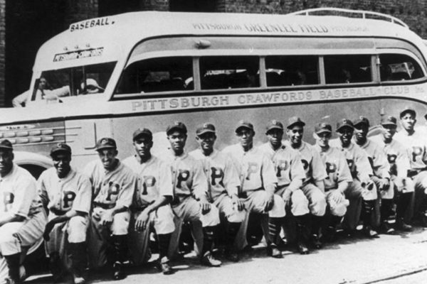 Baseball team lined up in front of a bus.