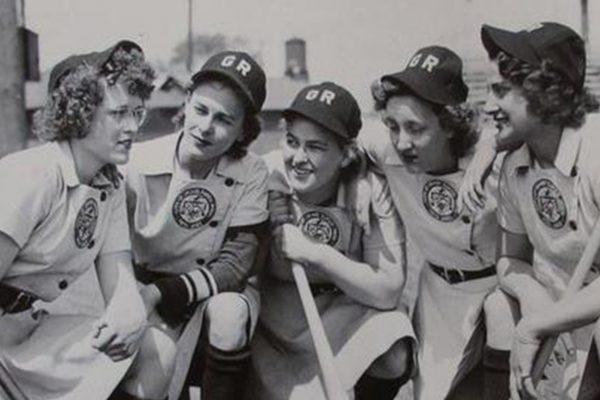 Women baseball players huddling.