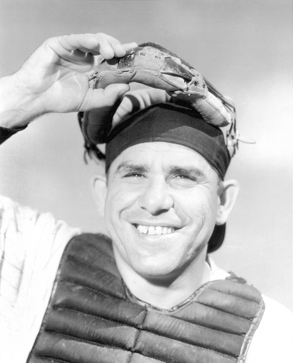 Yogi Berra lifting catcher's mask and smiling