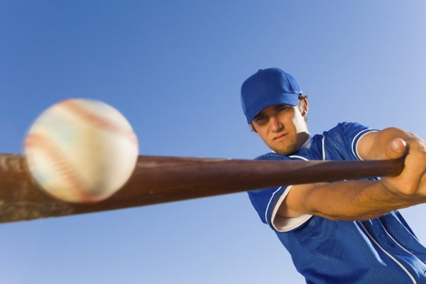 Male baseball player in blue uniform hitting a baseball