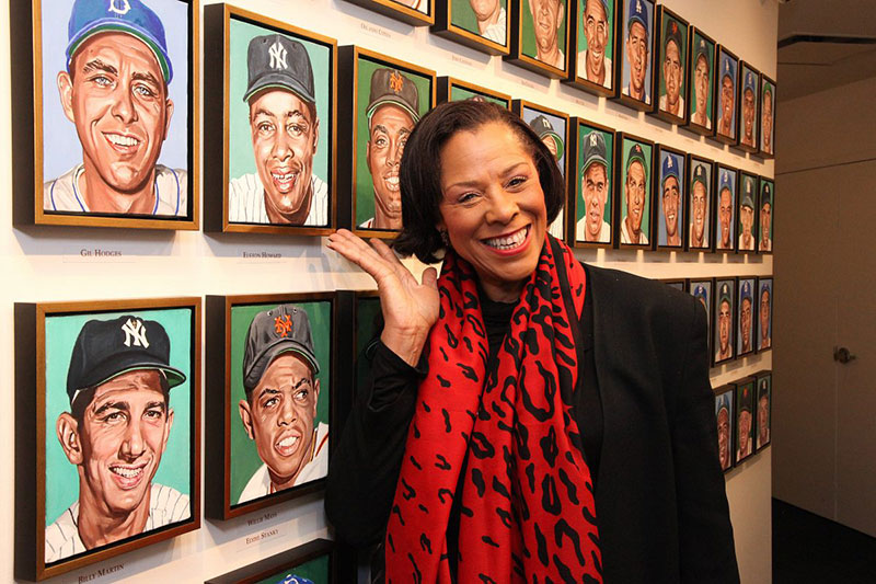 Cheryl Howard with the portrait of her dad, Elston Howard, as part of of Andy Jurinko's Golden Boys paintings