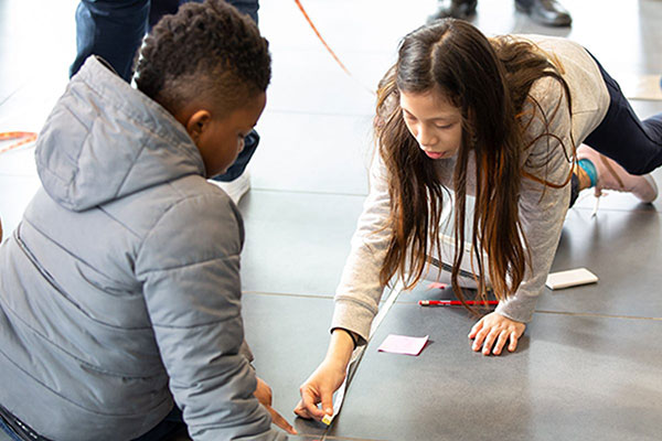 A young female and male student participating in an activity at the Museum