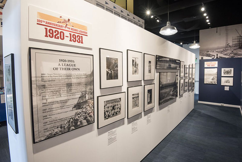 A wall of photos and information from 1920-1931 at the Discover Greatness exhibition
