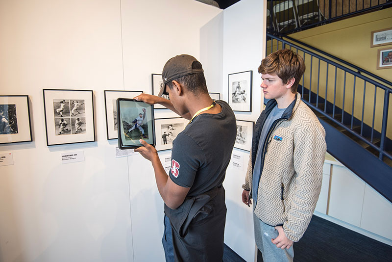 Two young men experiencing the augmented reality feature of the Discover Greatness exhibition