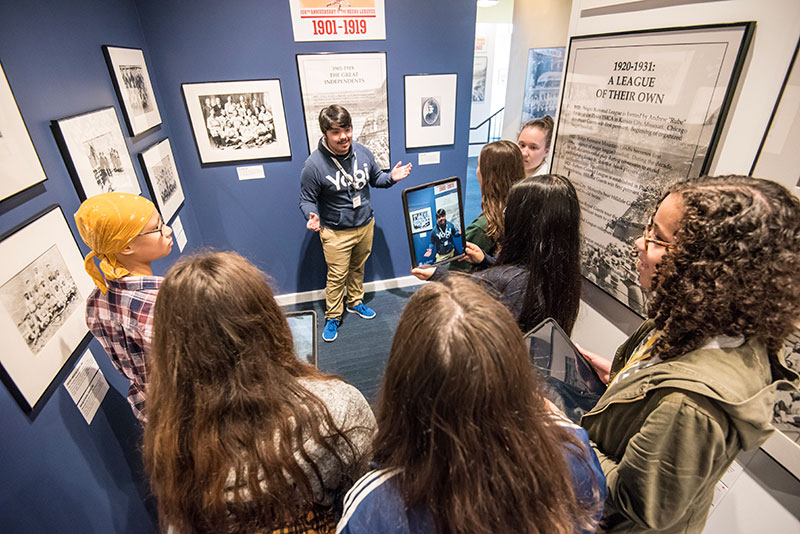 A Museum guide with a group of students at the Discover Greatness exhibition