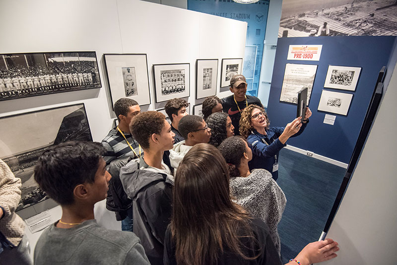 A Museum guide showing a group of students the augmented reality feature of the Discover Greatness exhibition