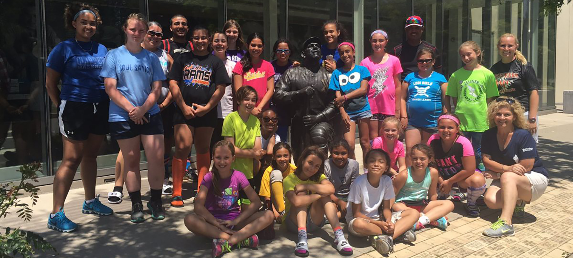 A group of children pose with the statue of Yogi Berra outside of his Museum
