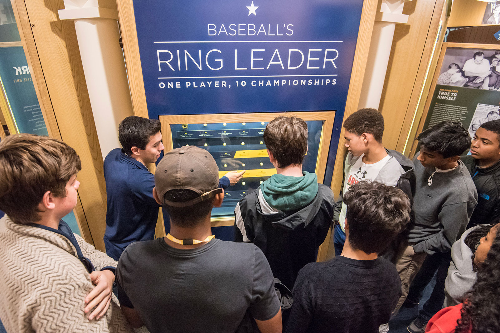 "A group of young people at the ""Baseball's Ring Leader"" wall of the Yogi Berra Museum"