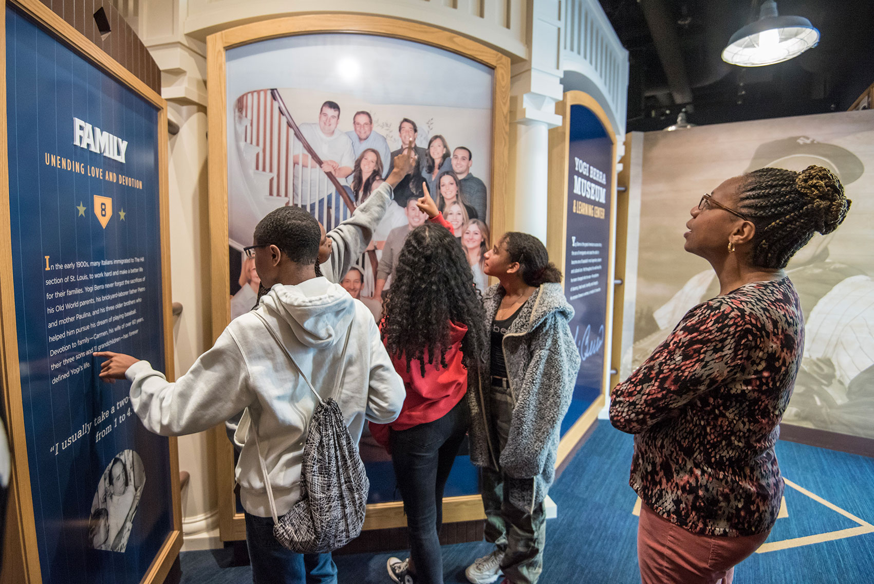 "A group of young people at the ""Family"" wall of the Yogi Berra Museum"