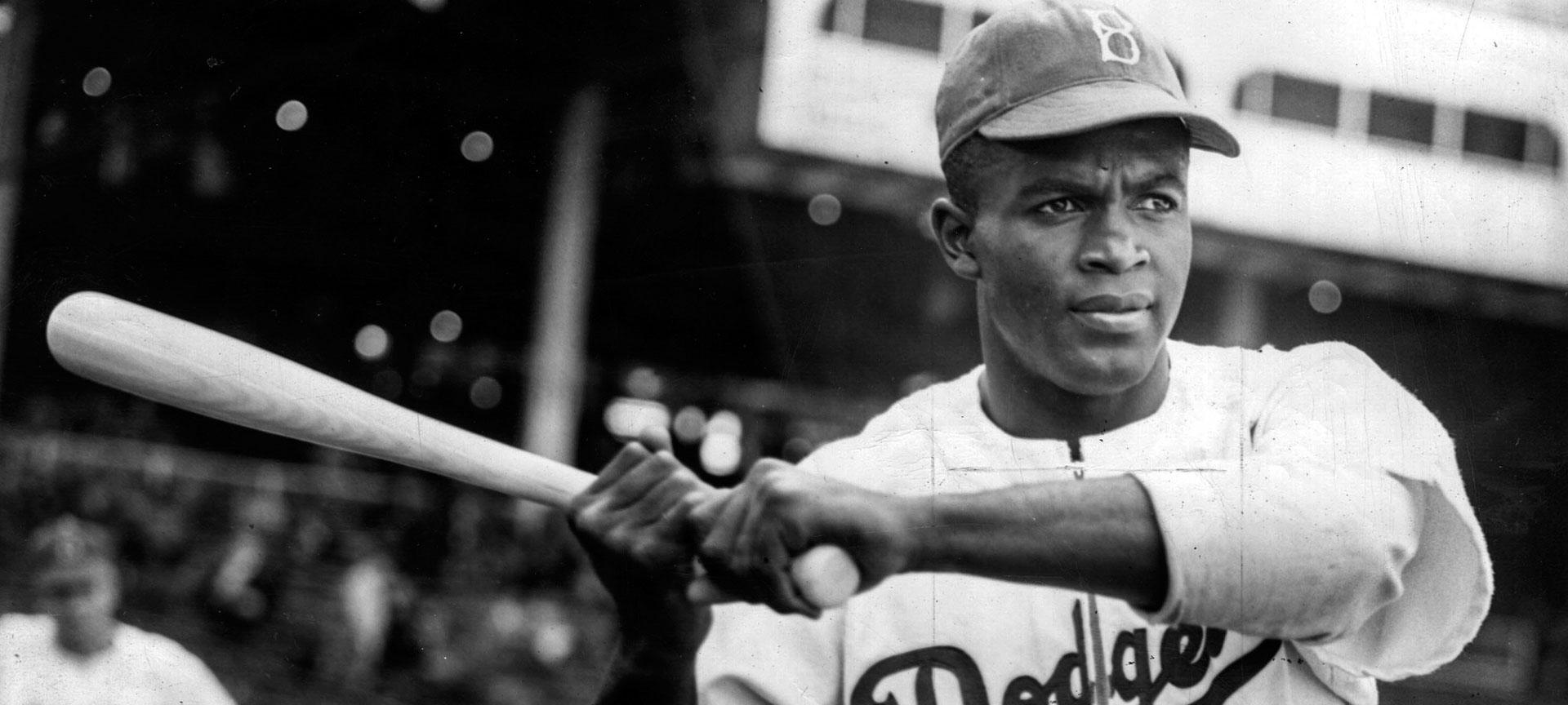 Jackie Robinson in a Brooklyn Dodgers uniform holding a baseball bat
