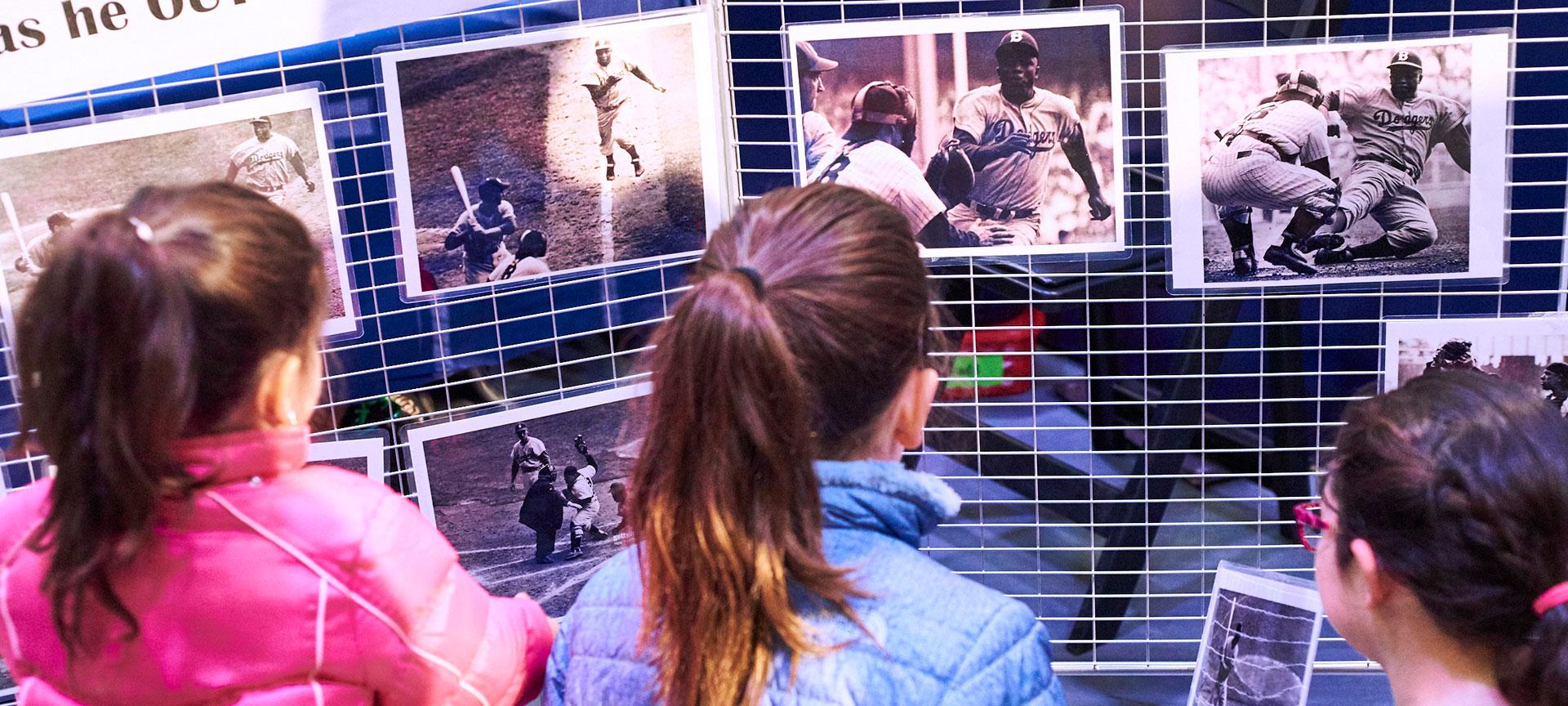 Three girls looking at photos of Jackie Robinson