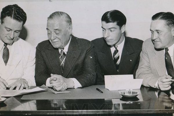 Three men in suits overlooking Lou Gehrig signing a contract