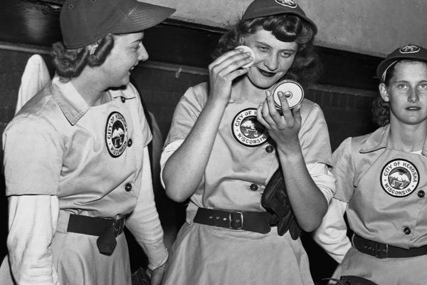 Three female baseball players from the Kenosha Comets in the dugout, with one applying makeup from a compact