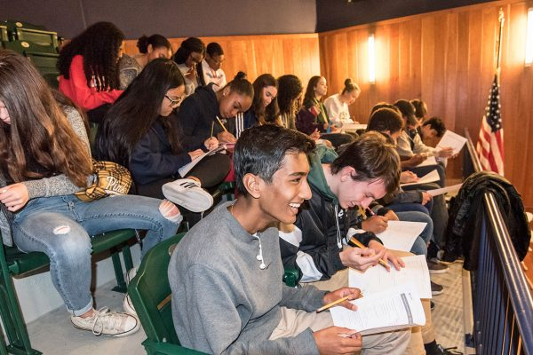 A large group of students participating in a writing activity in the seats of the Museum's auditorium