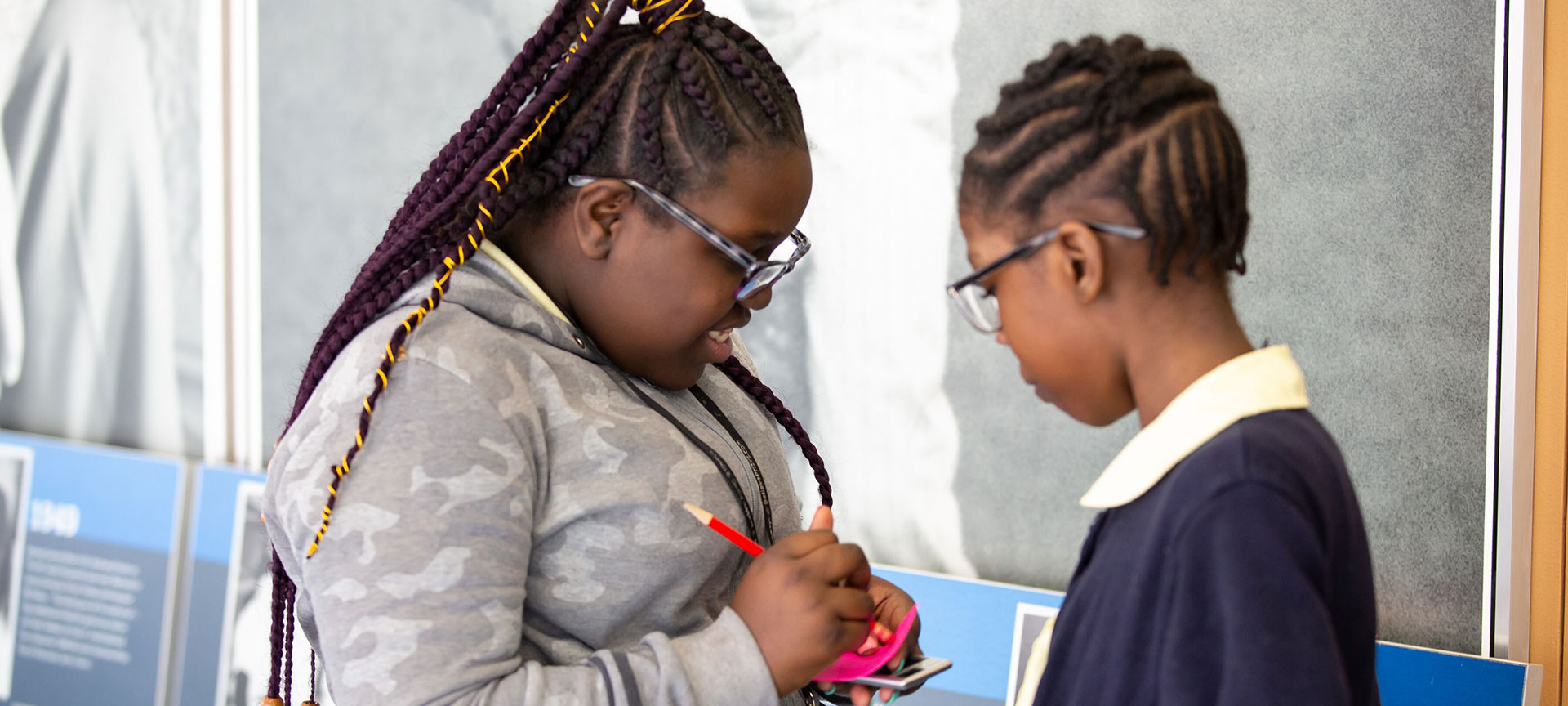 Two young female students participating in a writing activity
