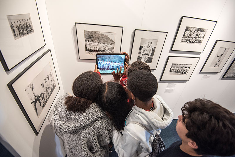 Students hold up an iPad with a colorized photo from the exhibit.