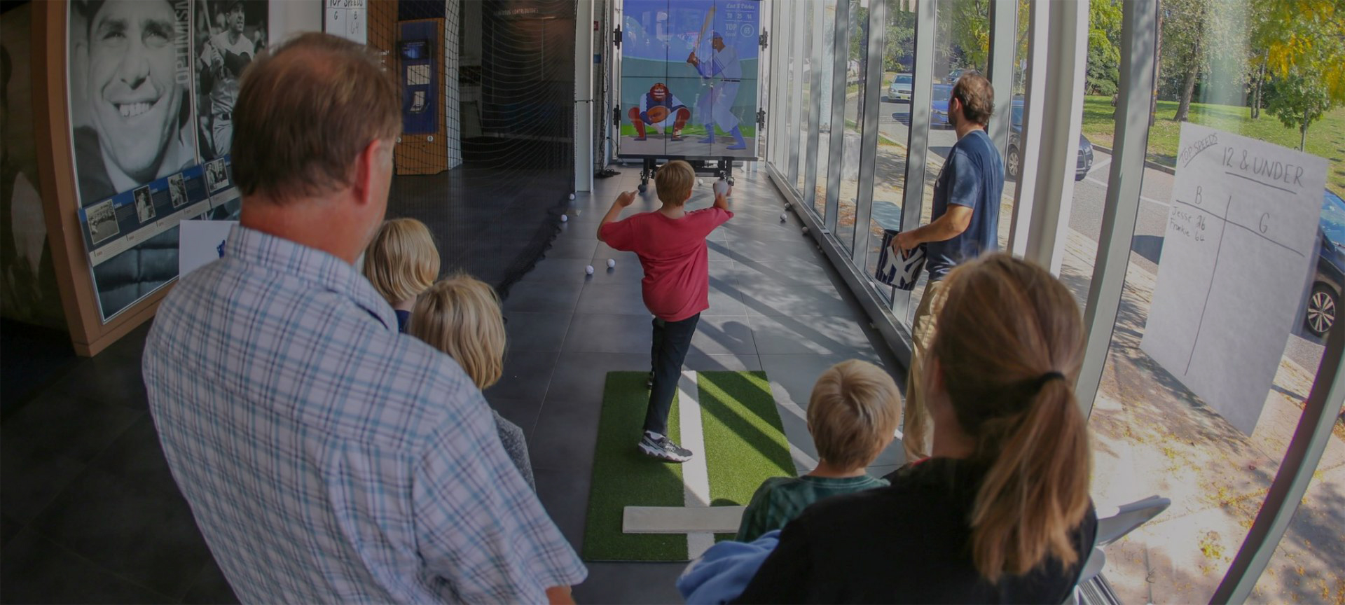 A boy throws a ball at a virtual pitching exhibit.