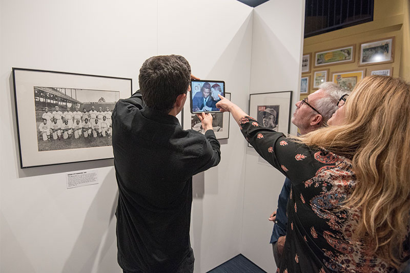 Viewers hold up and point at an iPad with colorized photos from the exhibit.